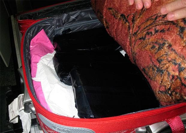 Droga estava escondida entra as roupas, dentro da bagagem da suspeita  (Foto: Divulgação/Polícia Federal )