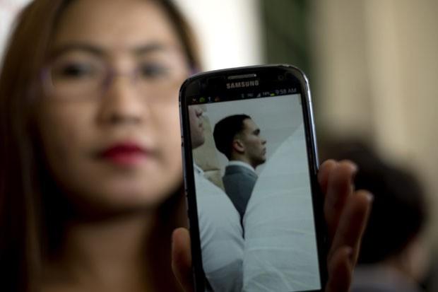 Marilou Laude, irmã de Jennifer Laude, morta nas Filipinas, mostra uma foto do fuzileiro naval americano Joseph Pemberton, acusado do crime, durante audiência nesta sexta-feira (19) (Foto: Noel Celis/AFP)