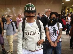 """Acorrentadas usam máscaras e capacetes com escrito """"Fifa"""". (Foto: Isabela Marinho / G1)"""