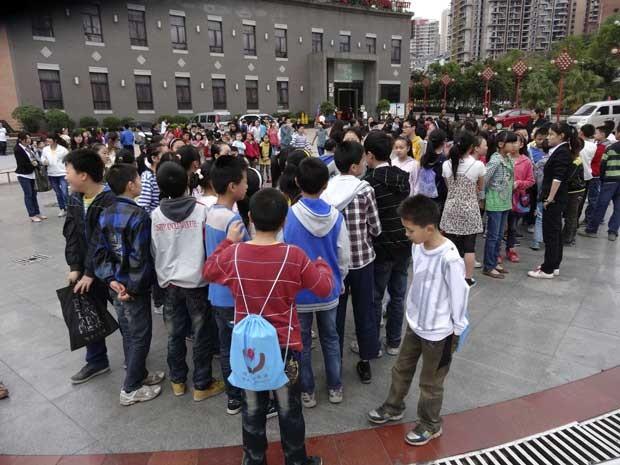 Alunos deixam escola e aguardam num pátio da cidade de Dazhoul, na província de Sichuam, após forte terremoto atingir a região. (Foto: Deng Liangkui / AP Photo)