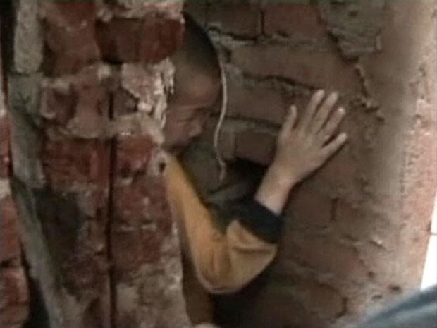Imagem de TV chinesa mostra menino de 5 anos preso em fenda entre paredes na China (Foto: CCTV/Reuters)