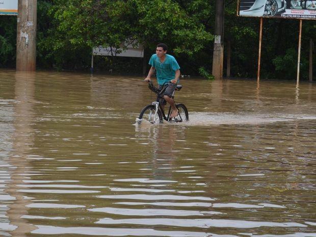 Homem se arrisca em bicicleta para atravessar rua alagada (Foto: Tássio Andrade/G1)