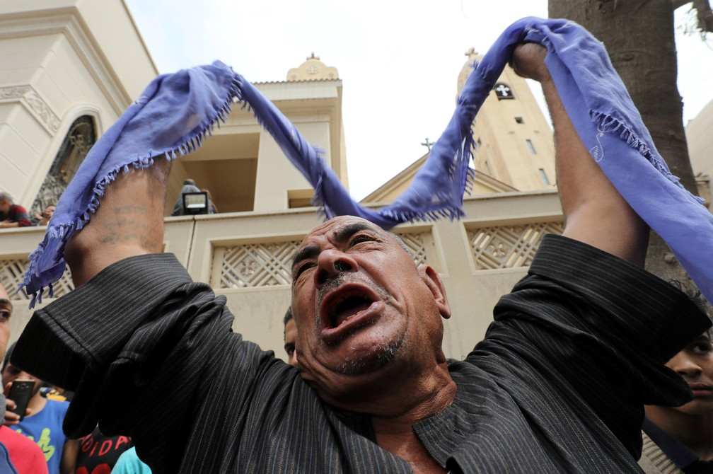 Familiar de vítima em frente a igreja alvo de ataque em Tanta, no Egito, neste domingo (9) (Foto: Mohamed Abd El Ghany/Reuters)