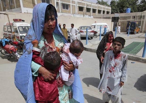 Ferida, mãe leva seus filhos, também feridos, a hospital na cidade paquistanesa de Quetta, após atentado a bomba nesta terça-feira (21). O ataque, que mirava um comboio das forças de segurança, matou pelo menos um civil e deixou vários feridos (Foto: Arshad Butt/AP)