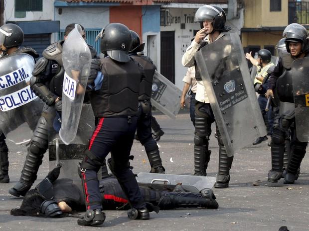 Policiais cercam corpo de colega atropelado por um ônibus durante protesto em San Cristóbal, na Venezuela, na terça (29) (Foto: Reuters/Carlos Eduardo Ramirez)