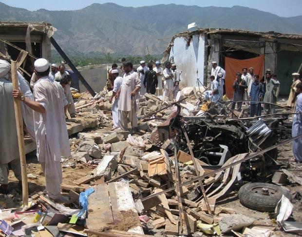 Moradores procuram vítimas entre destroços de mercado explodido em Bajaur nesta quinta-feira (26) (Foto: AFP)