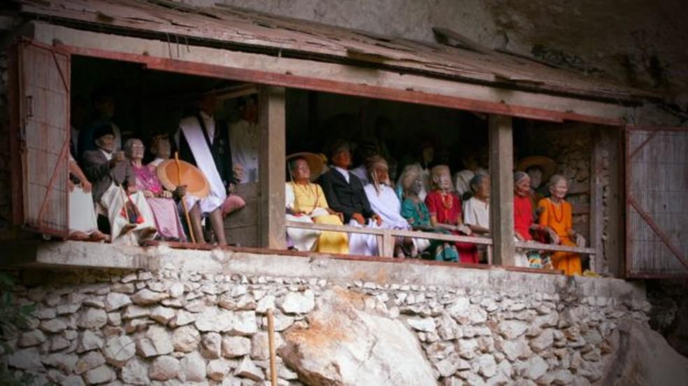 Outra tradição da região são os tau taus, imagens de homens e mulheres que morreram cuidadosamente esculpidas na madeira e decoradas com objetos pessoais  (Foto: BBC)