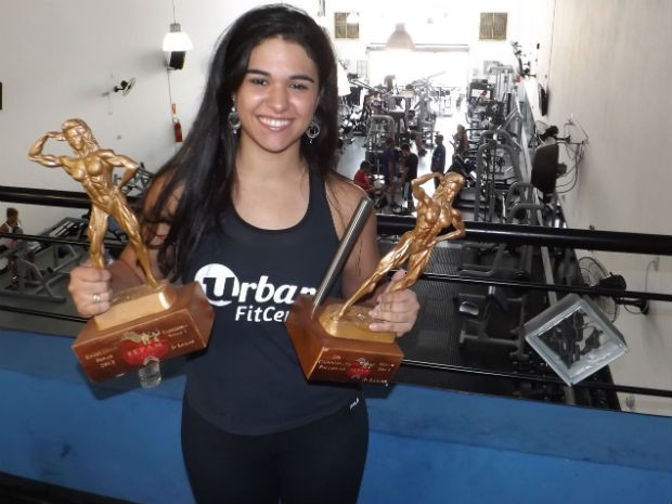 Natália exibe troféus conquistados no fisiculturismo  (Foto: Renata Marconi/G1)