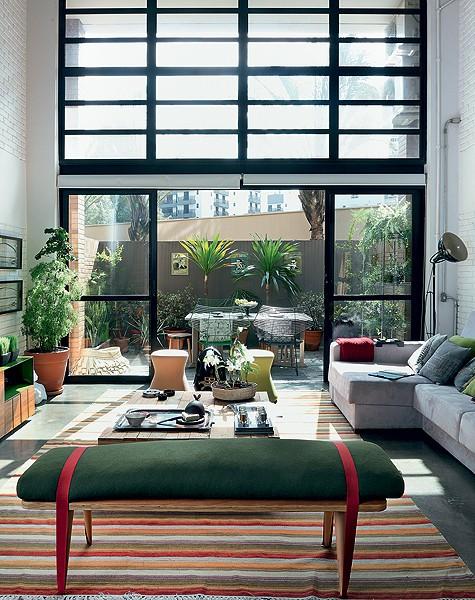 A sala do apartamento tem jeito de casa fresca, graças ao acesso ao terraço e o pé-direito duplo com janelas. Muitas plantas completam o visual. Projeto da arquiteta Bruna Riscali (Foto: Evelyn Müller/Casa e Jardim)