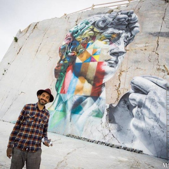 Kobra posa em frente ao seu novo mural em Carrara, na Itália, inspirado na obra Davi, de Michelangelo (Foto:  Matteo Dunchi/Divulgação)