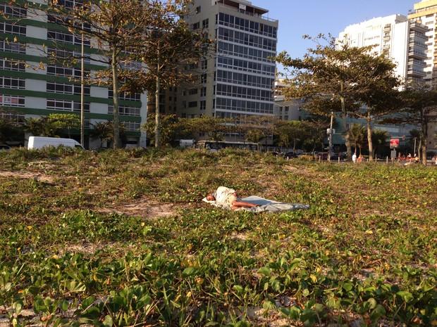 Morador de rua dorme em vegetação em Ipanema, na altura do Posto 10 (Foto: Káthia Mello/G1)