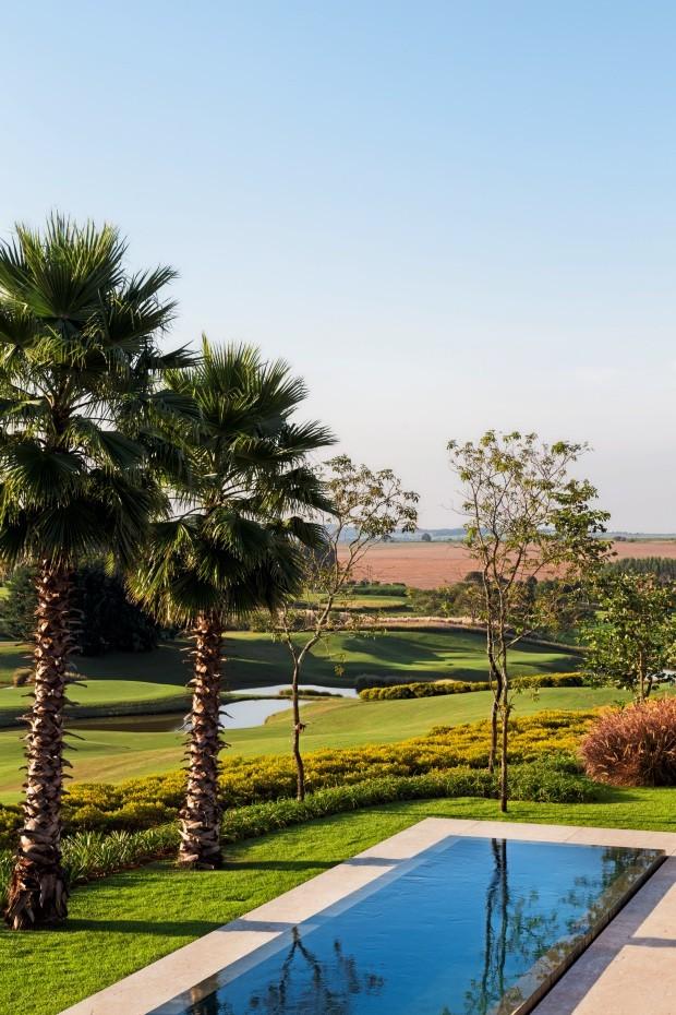 Lateral. Como o condomínio não permite muros, é como se o campo de golfe fizesse parte do quintal. Ao lado das palmeiras, três ipês. Como forração, lírios (Foto: Yuri Seródio / Divulgação)