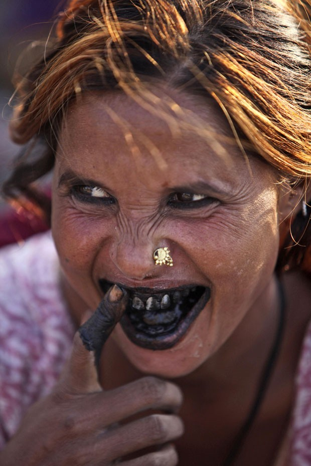 Uma indiana foi fotografada na quinta-feira (4) usansi carvão para limpar os dentes em Jammu, na Índia. (Foto: Channi Anand/AP)