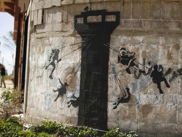 Outra obra com tema infantil atribuída a Banksy é vista em um muro em Biet Hanoun, no norte da Faixa de Gaza. O artista de rua britânico postou fotos em seu site mostrando obras criadas na região destruída após bombardeios, além de um vídeo 'turistico' (Foto: Suhaib Salem/Reuters)
