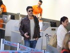De óculos escuros, Junno embarca no aeroporto do Rio de Janeiro