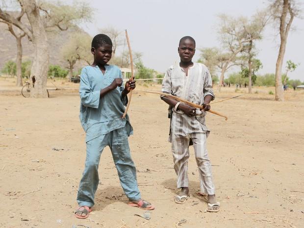 Crianças carregam armas em Kerawa, nos Camarões, em foto de 16 de março (Foto: Joe Penney/ Reuters )
