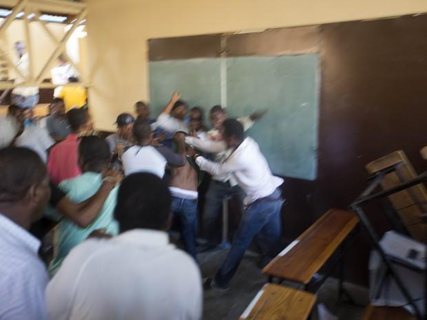 Ponto de votação em Porto Príncipe foi fechado após uma briga. Um jovem atirou cédulas e pedras (Foto: Dieu Nalio Chery/AP)