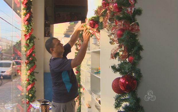 Lojista enfeitando a vitrine com decorações natalinas (Foto: Reprodução/TV Amapá)
