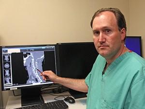 Médico Craig Cook mostra raio-X com fratura de pescoço que ocorreu em trampolim (Foto: Rick Bowmer/AP)