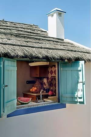 """Os tons de azul e branco das fachadas remetem a Portugal, país onde está localizada a casa de praia, mas elementos rústicos, como o sapé visto no teto, fazem-na também """"passear"""" por outros cantos do mundo (Foto: Casa e Jardim)"""