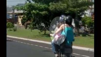 Passageira de moto segura criança sem capacete no trânsito de Franca, SP