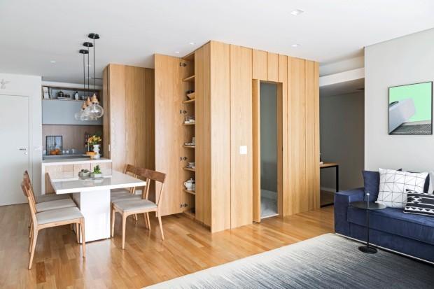 As folhas da madeira revestem a continuação da parede e a porta do lavabo, criando a sensação de uma caixa no meio da sala (Foto: Julia Ribeiro / Divulgação)