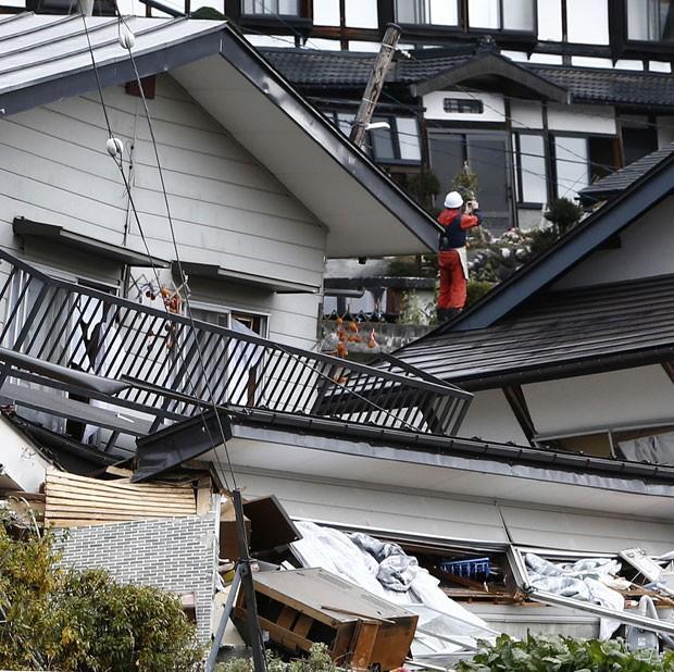 Morador é visto neste domingo (23) em casa que desabou após terremoto em Hakuba, no centro do Japão (Foto: Jiji Press/AFP)