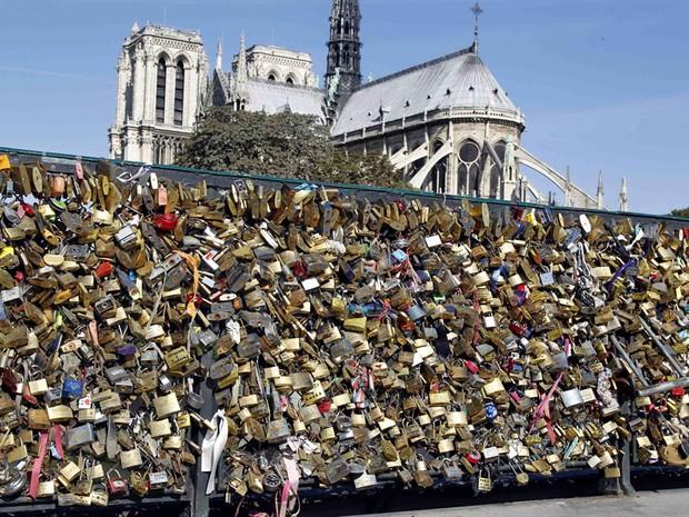 Milhares de cadeados colocados por casais em Paris nas grades do Pont de l'Archeveche  são vistos em frente à Catedral de Notre Dame (Foto: Charles Platiau/Reuters)