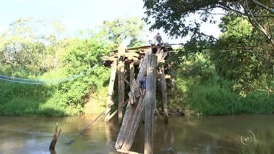 Jovens escalam estrutura de ponte  de madeira que caiu há três meses