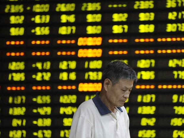 Investidor é visto em frente ao painel eletrônico com informações da bolsa em uma corretora de Huaibei, na China. As ações no país caíram mais de 8%, sua maior queda em um dia em mais de oito anos  (Foto: Reuters)