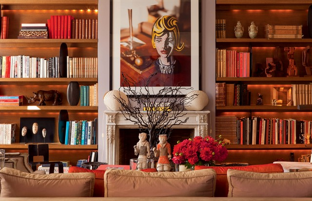 A biblioteca do casal, com objetos garimpados ao longo da vida, como máscaras africanas, esculturas de guerreiros chineses compradas em Hong Kong e uma foto do apartamento do art dealer Leo Castelli, clicada por Prosper. (Foto: Emilia Brandão)
