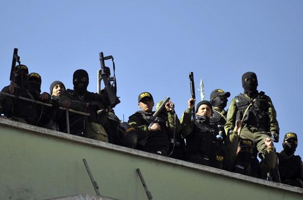 Policiais amotinados ficam no telhado da central da inteligência da polícia em La Paz, na sexta feira (22) (Foto: AFP/PHOTO/Aizar Raldes)