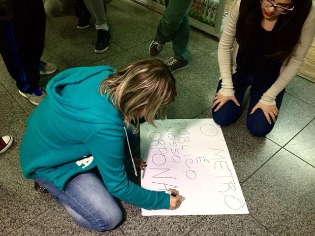 Mulher escreve cartaz em manifestação contra o abuso sexual no Metrô de São Paulo (Foto: Anne Barbosa/G1)