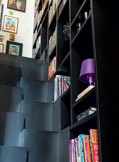 A escada tipo Santos Dumont, que leva ao mezanino, integra-se à grande estante, na lateral direita, formando um único bloco (Foto: Edu Castello/Editora Globo)
