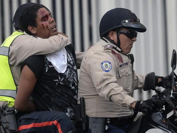 Ativista ferido é preso pela polícia durante um protesto contra o governo da Venezuela em Caracas (Foto: Leo Ramirez/AFP)
