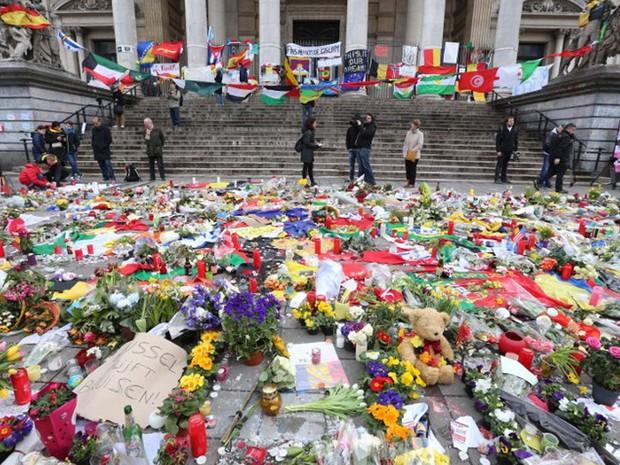 Flores e velas são colocadas na Place de la Bourse, em Bruxelas, na Bélgica, neste domingo (27) em uma homenagem às vítimas dos ataques do Estado Islâmicos que deixaram 31 mortos e 270 feridos (Foto: Nicolas Maeterlinck / AFP)