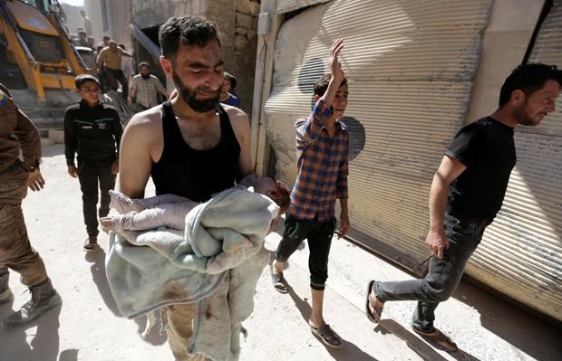 Socorrista chora ao carregar corpo de uma criança que morreu após ataque aéreo em área controlada pelos rebeldes na cidade Maaret al-Numan, na província de Idlib, no domingo (12) (Foto: Khalil Ashawi/Reuters)