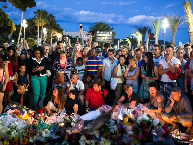 Pessoas se reúnem em um memorial em homenagem às vítimas do ataque com um caminhão em Nice, na França, durante a festa do dia da queda da bastilha. Mais de 80 pessoas morreram e dezenas ficaram feridas (Foto: Laurent Cipriani/AP)