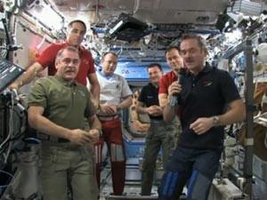 Chris Hadfield, com o microfone, passa o comando da missão para Pavel Vinogradov, à esquerda (Foto: Nasa TV/Reprodução)