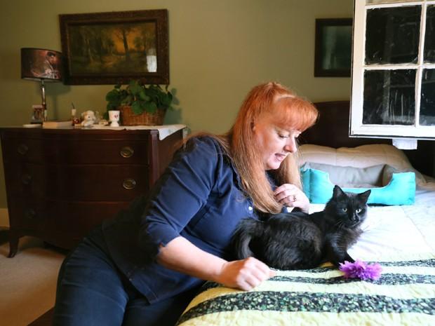 Laurie Sullivan posa ao lado do gato que encontrou com uma flecha no pescoço em frente à sua casa, em Battle Creek, Michigan, na quinta (5) (Foto: Mark Bugnaski/Kalamazoo Gazette-MLive Media Group via AP)