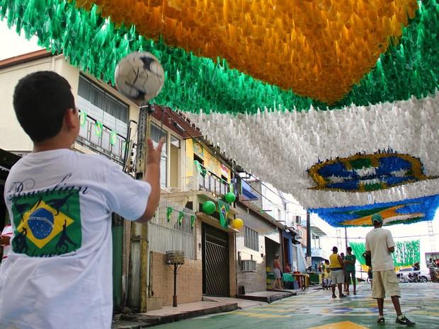 Menino brinca de bola da rua enfeitada para o Mundial de Futebol (Foto: Jamile Alves/G1 AM)
