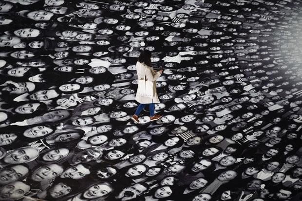 Mulher caminha sob retratos de parisienses anônimos (Foto: Martin Bureau/AFP)