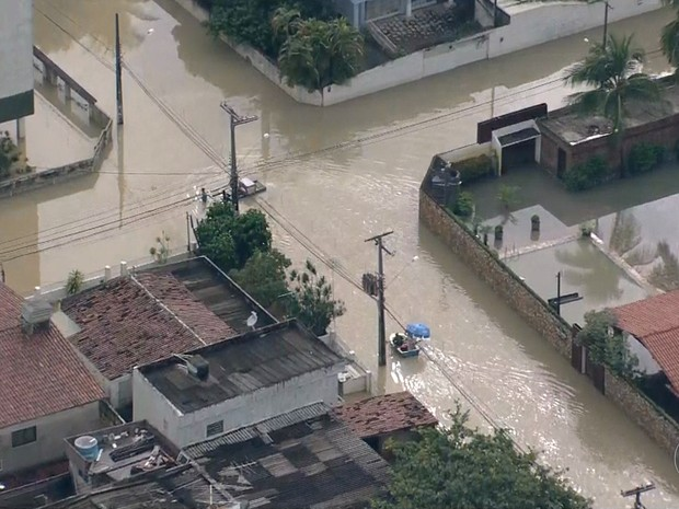 Para sair de casa nesta terça-feira (10), moradores tiveram que usar barcos (Foto: Reprodução / TV Globo)