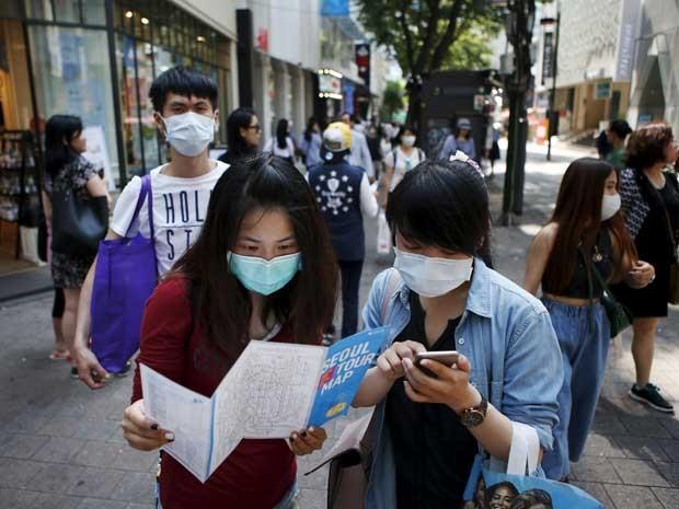 Contra surto, turistas e sul-coreanos usam máscaras nas ruas. (Foto: Kim Hong-ji / Reuters)