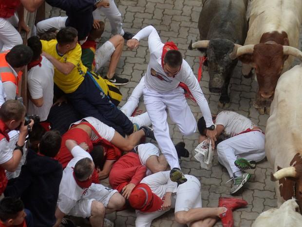 Corredores caem no chão durante festival de São Firmino, na Espanha (Foto: Vincent West / Reuters)