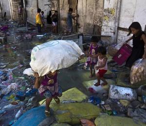 Sobreviventes do tufão Haiyan procuram restos de comida pelas ruas destruídas de Tacloban, nas Filipinas. O governo elevou nesta segunda-feira (18) para quase 4 mil o número oficial de mortos (Foto: AP Photo/David Guttenfelder)