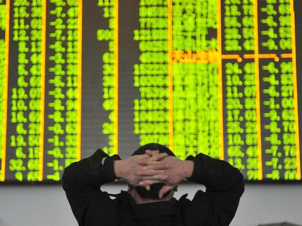 Investidor observa um painel com dados da bolsa em Hangzhou, na China. A Bolsa de Xangai encerrou a sessão de terça-feira (26) em forte queda de 6,42%, em consequência das vendas em massa de ações, causadas por baixa no preço do petróleo (Foto: Reuters/China Daily)