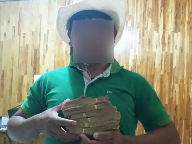 Fotografia divulgada pela Polícia Civil mostra índio da etnia Enawenê-nawê com blocos de cédulas: segundo investigações, caminhonetes foram pagas com dinheiro em espécie. (Foto: Polícia Civil/Divulgação)