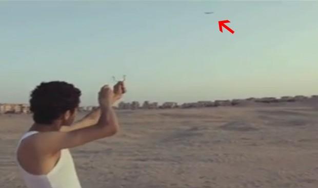 Jovem mira com o estilingue em direção à aeronave... (Foto: Reprodução)