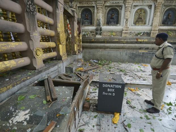 Oficial de segurança inspeciona o local de uma explosão no complexo do Templo Mahabodhi neste domingo (7) na Índia (Foto: Manish Bhandari/ AP)